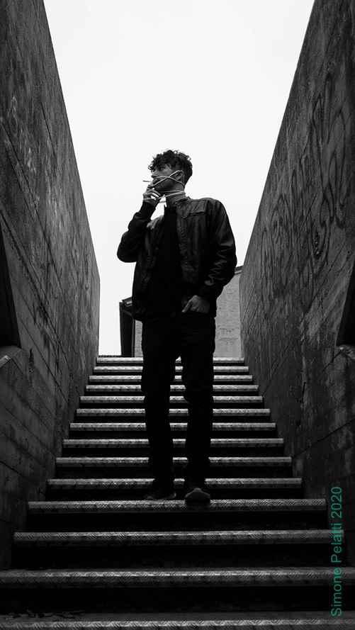 ragazzo vestito di nero scende dalle scale metalliche fumando una sigaretta
