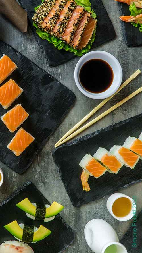piatti di cucina orientale e sushi visti dall'alto su tavolo grigio