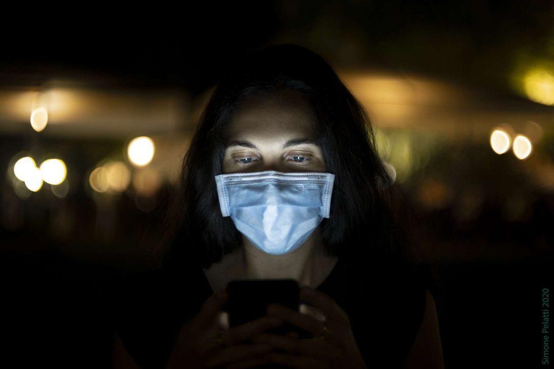 Somewhere far beyond (self social distancing) - Jessica in primo piano guarda lo schermo del cellulare, che le illumina il viso semicoperto dalla mascherina azzurra. Dietro di lei, in distanza, sono le luci arancioni di un locale all'aperto. 50mm, f 1.4, 1-13 sec, ISO 320. Simone Pelatti 2020