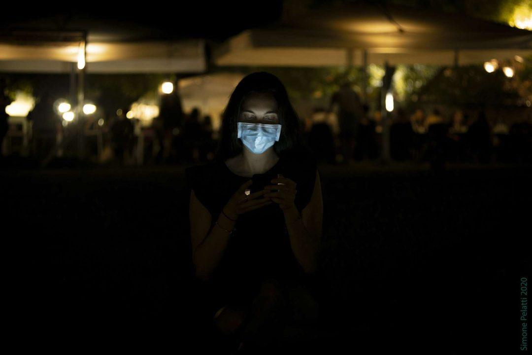 Among but not too much (self social distancing) - Jessica guarda lo schermo del cellulare, che le illumina il viso semicoperto dalla mascherina azzurra. Dietro di lei, in distanza, sono le luci arancioni di un locale all'aperto. 35mm, f 2.0, 1-20 sec, ISO 400. Simone Pelatti 2020