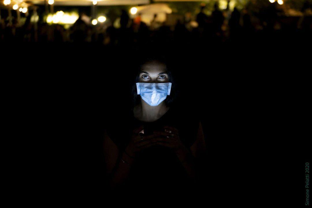 It's all in my mind (self social distancing) - Avvolta nel buio della sera inoltrata, Jessica alza gli occhi dallo schermo del cellulare, che le illumina il viso semicoperto dalla mascherina azzurra. Dietro di lei, sopra la sua testa in prospettiva, sono le luci arancioni di un locale all'aperto. 35mm, f 1.7, 1-20 sec, ISO 400. Simone Pelatti 2020